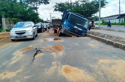Caminhão cai em buraco após parte da pista ceder